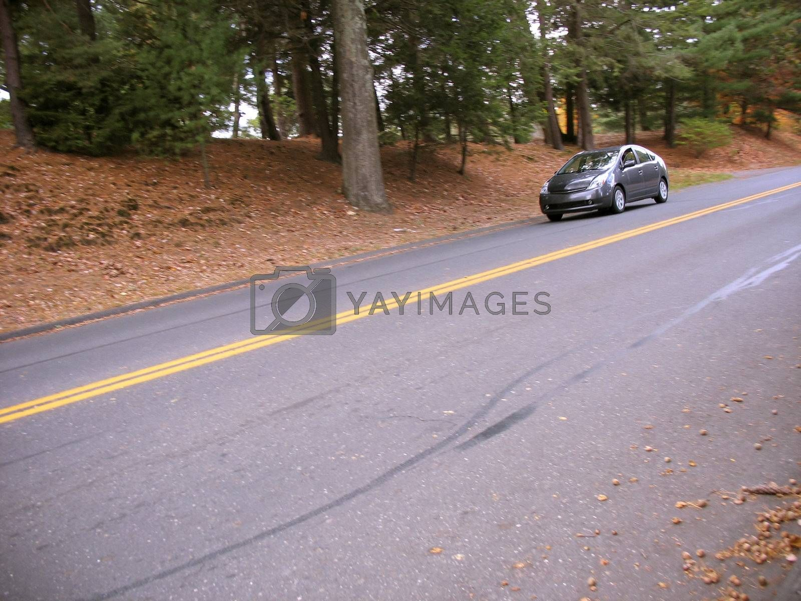 A modern hybrid vehicle driving down the road on a nice autumn day.