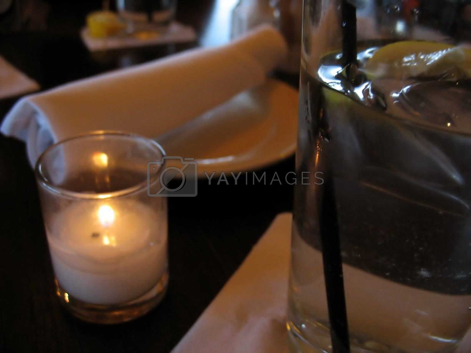 A closeup of a table at a restaurant - waiting to be served.  in the foreground is some water with lemon, and a romantic little candle.