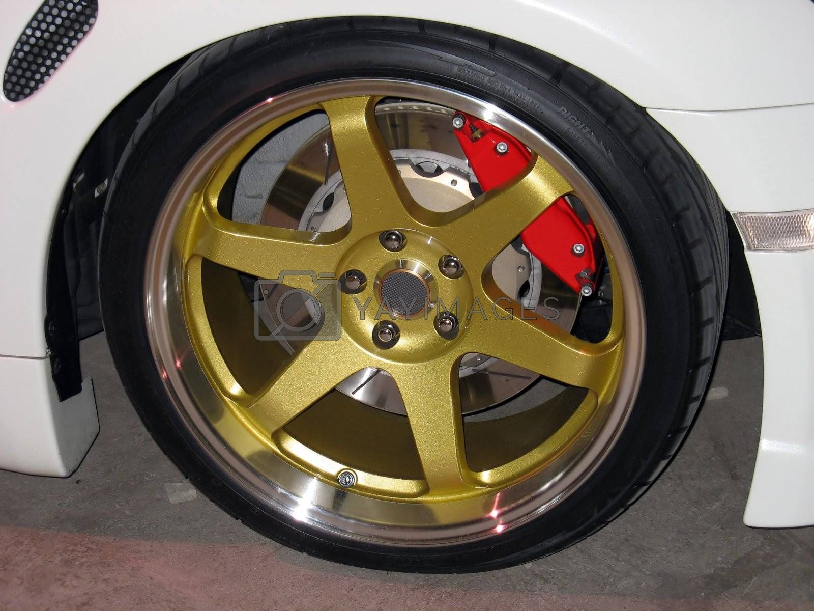 custom gold rims on a white sportscar complete with performance brakes