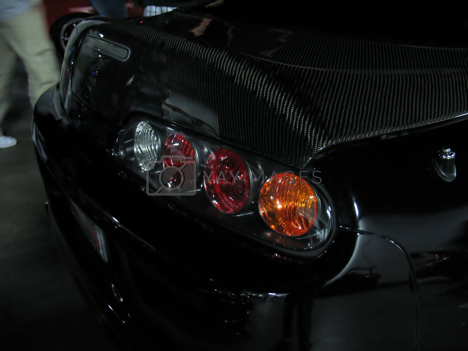 a closeup of a customized import sports car - complete with a carbon fiber trunk.