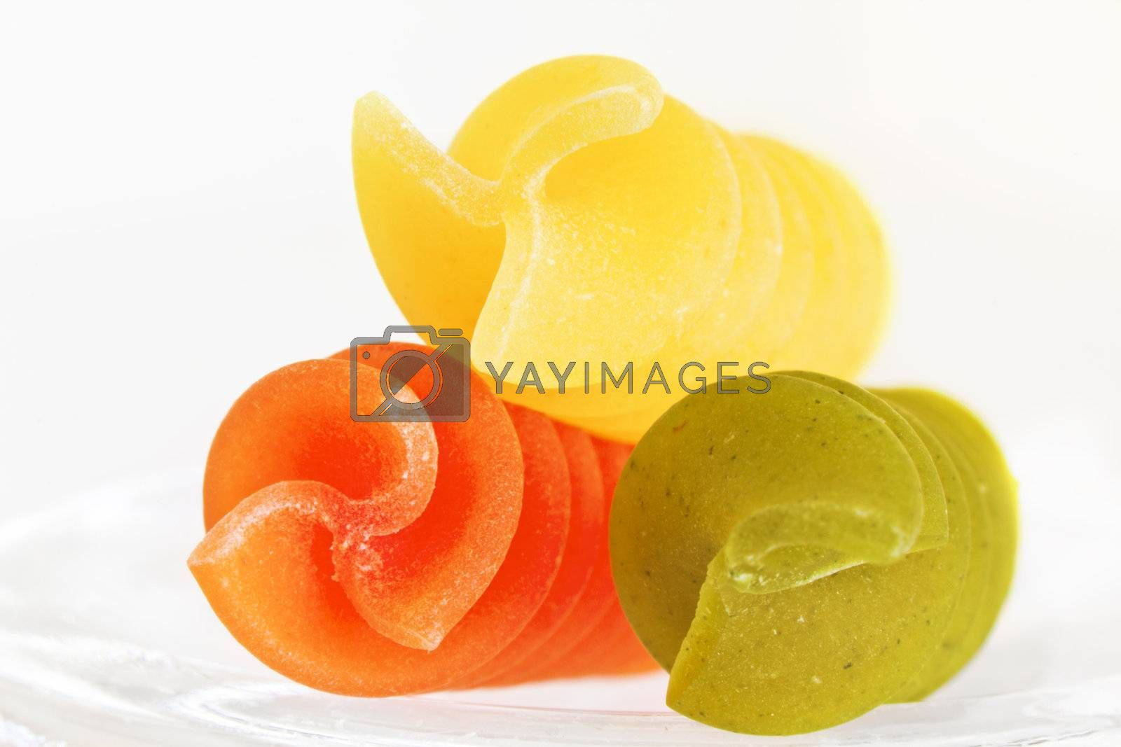 Three colorful raw fusillis on a white background