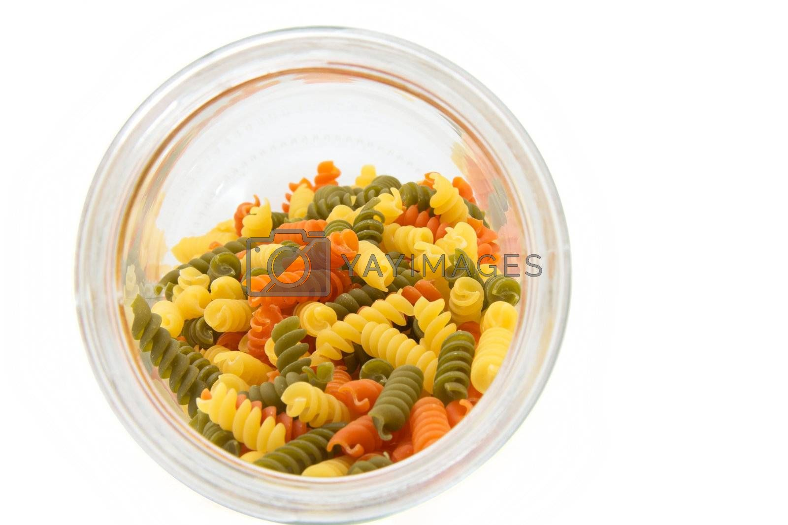 Colorful raw fusilli in a glass jar on a white background