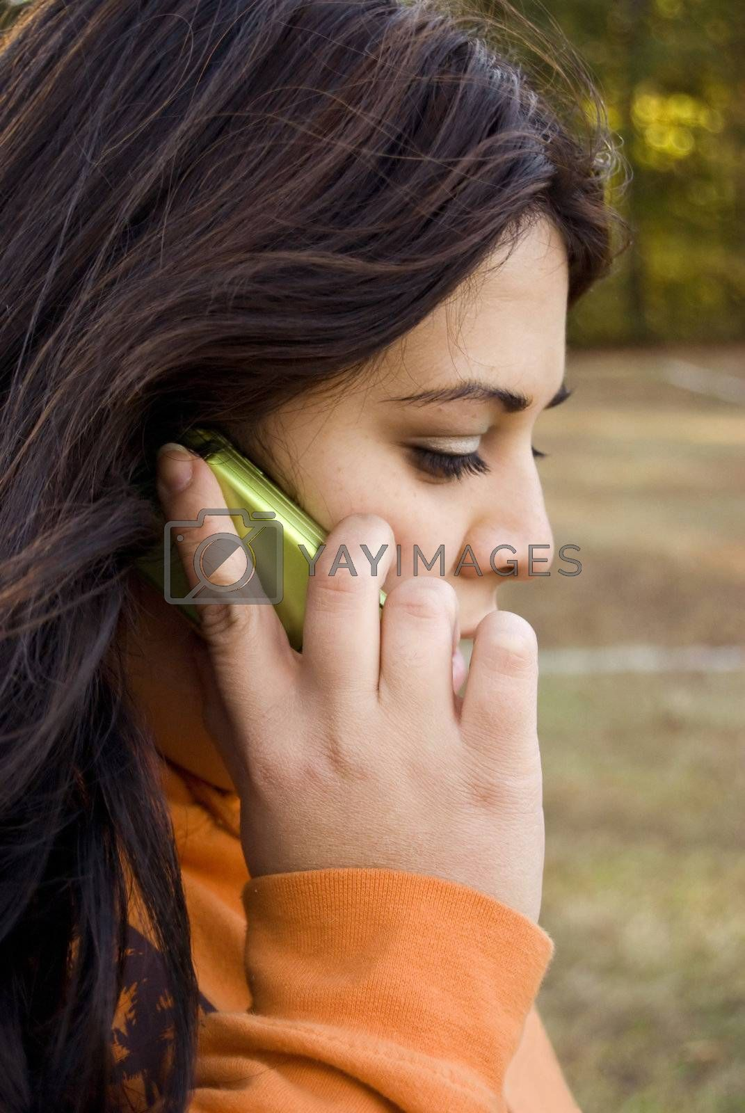 A beautiful young woman of latin descent talking on a cell phone.