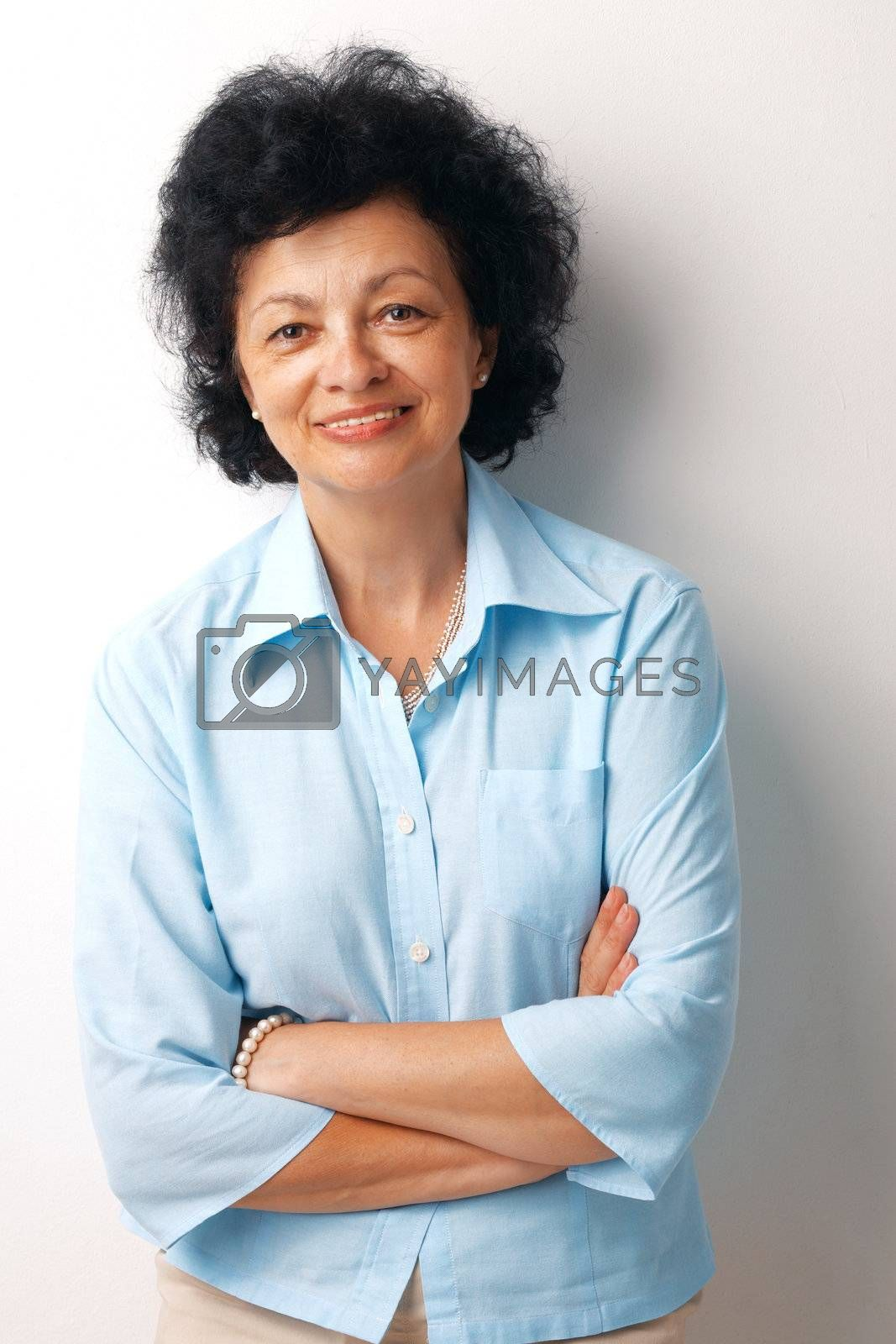 Portrait of a happy old woman with her hands folded on white background