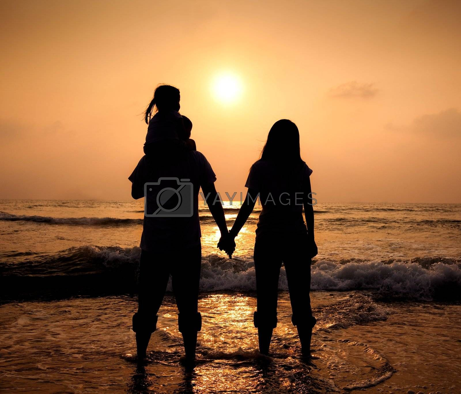 The silhouette of loving asian family walking while holding hands on beach at sunset by tomwang