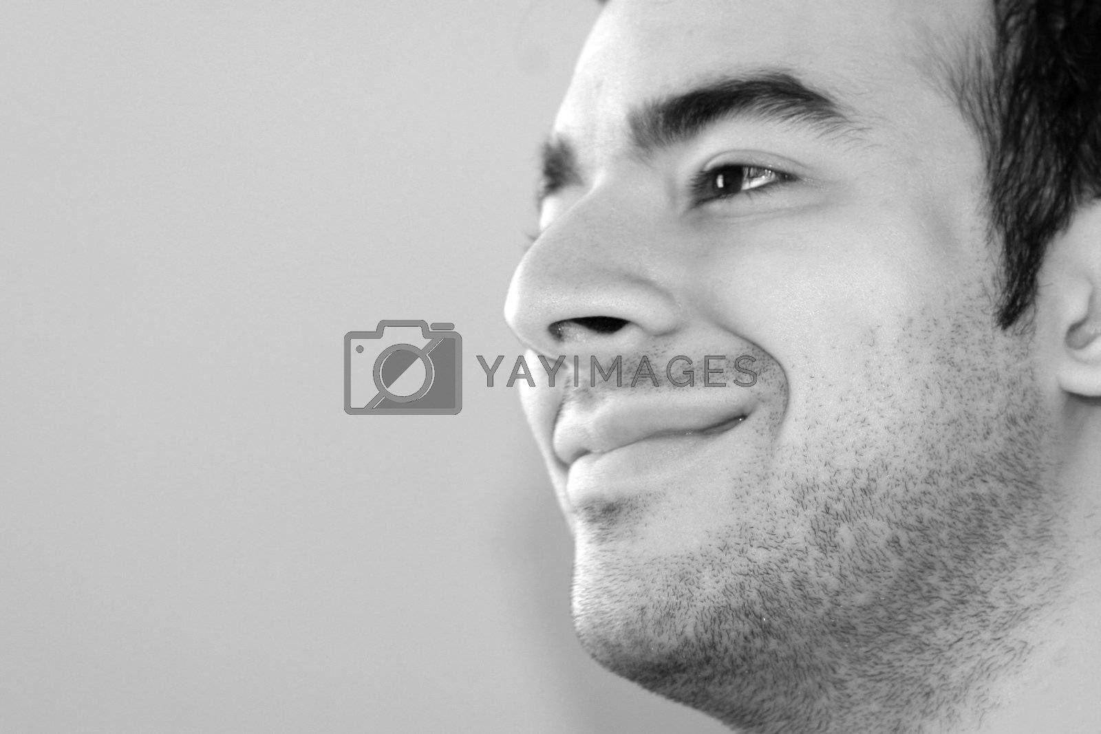 Black and white portrait of a young man smiling - plenty of copy space to the left.
