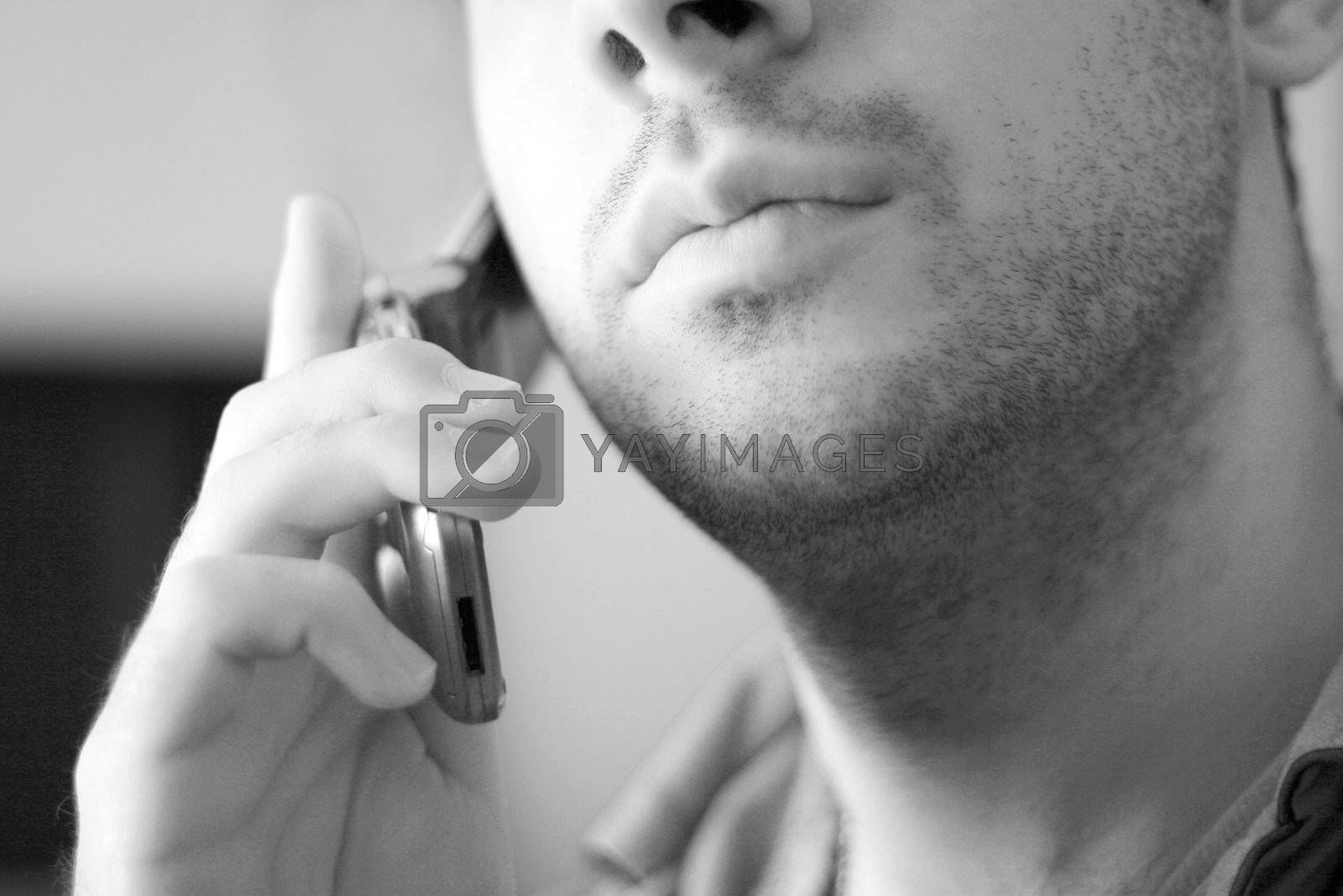 Black and white portrait of an unshaven young man talking on his celly phone.
