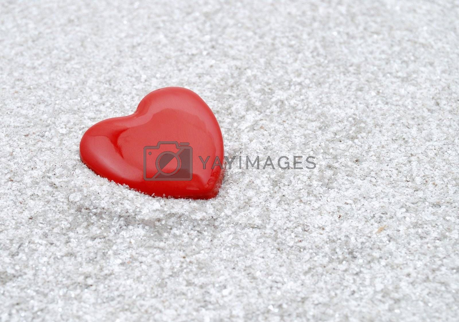 Lonely red heart fallen in grey ashes