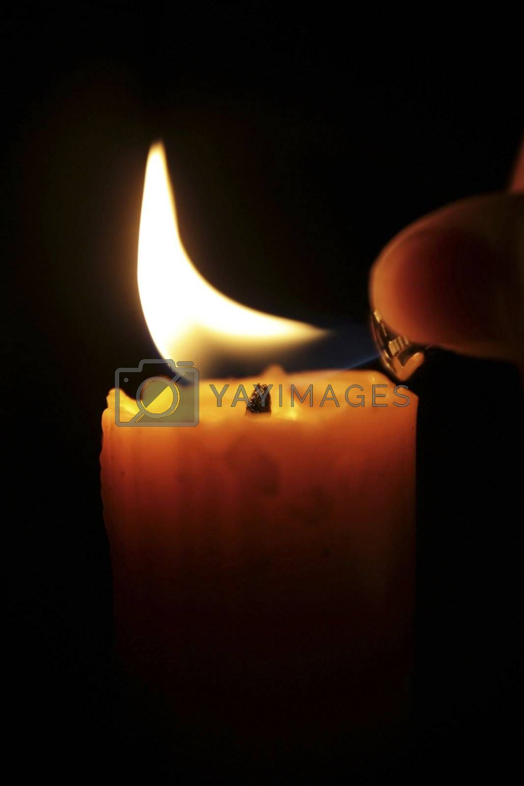 hand lighting candle in the dark