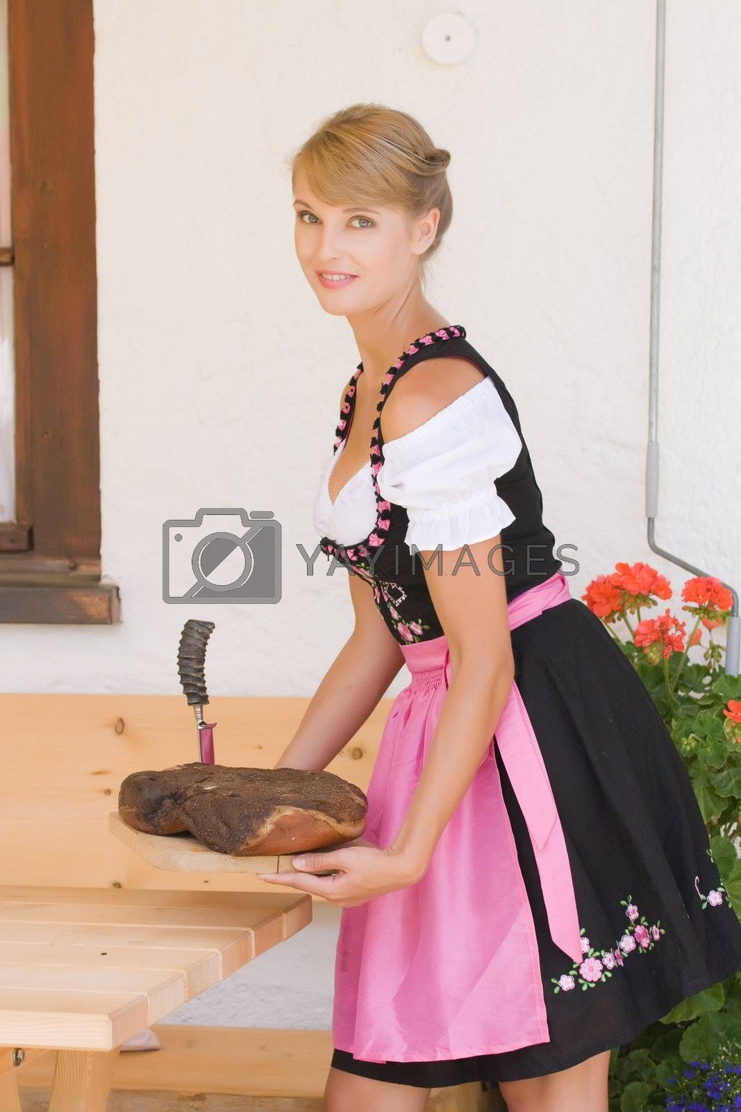 Bavarian Dirndl woman serving a bacon on a plate Alm