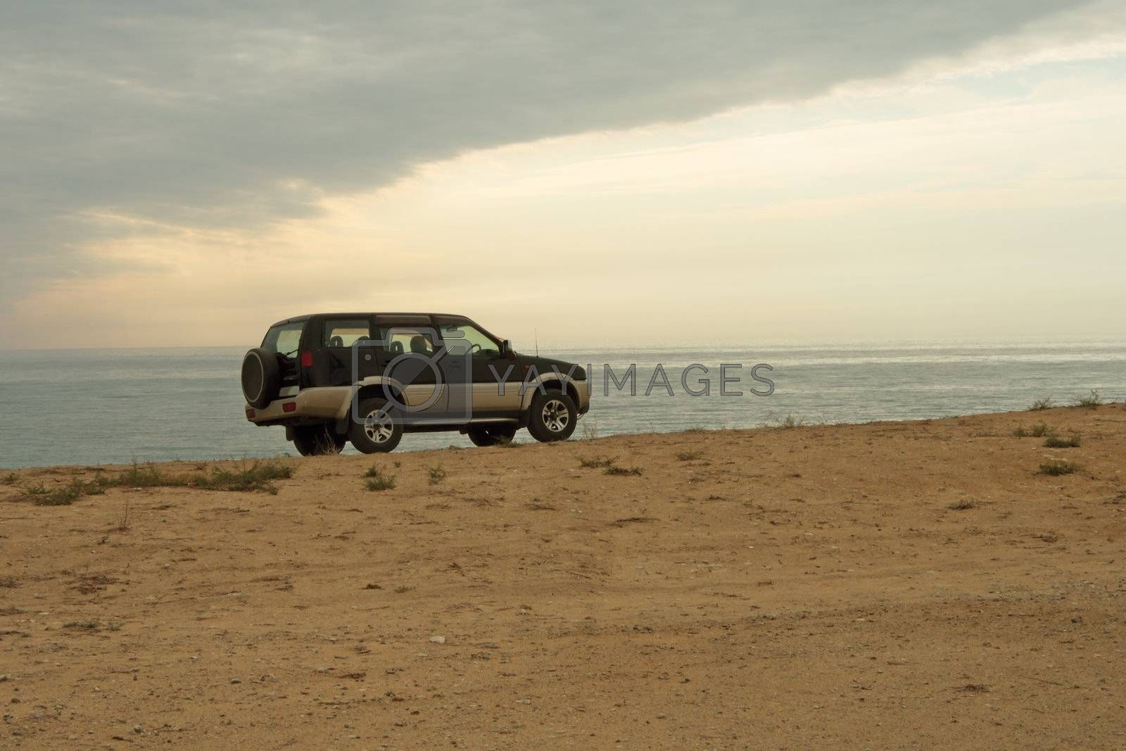 Jeep car is on the edge of the cliff against the sea.