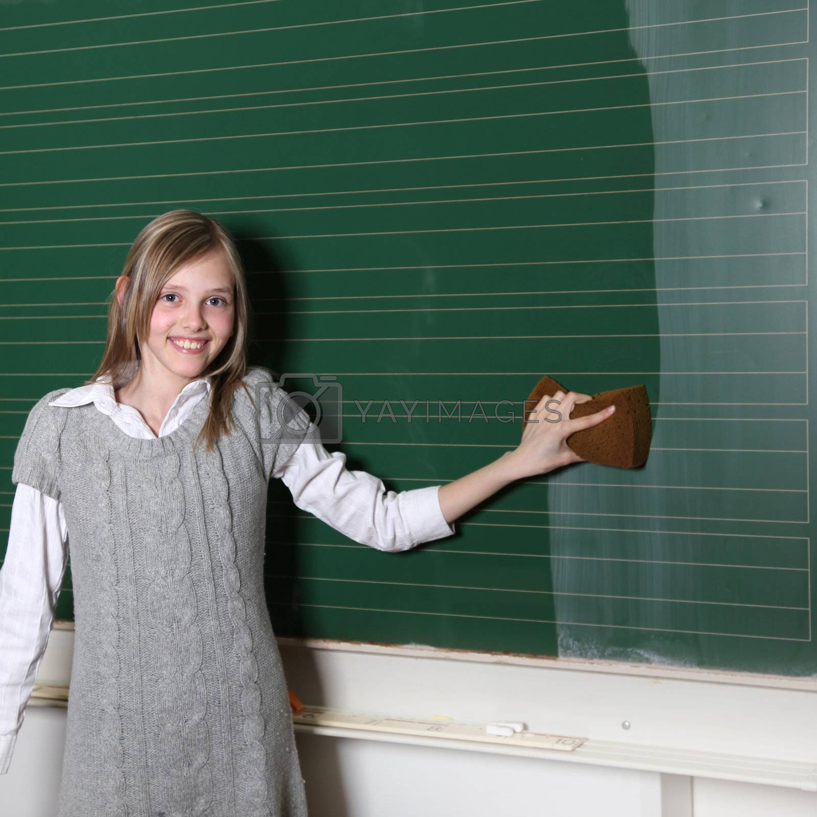 School girls at the blackboard. She wipes the table and smiles - Copy Space