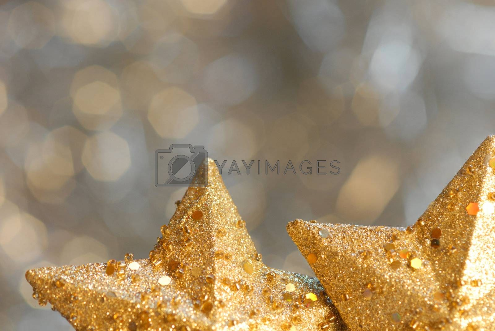 Christmas background with two gold stars blurred foreground