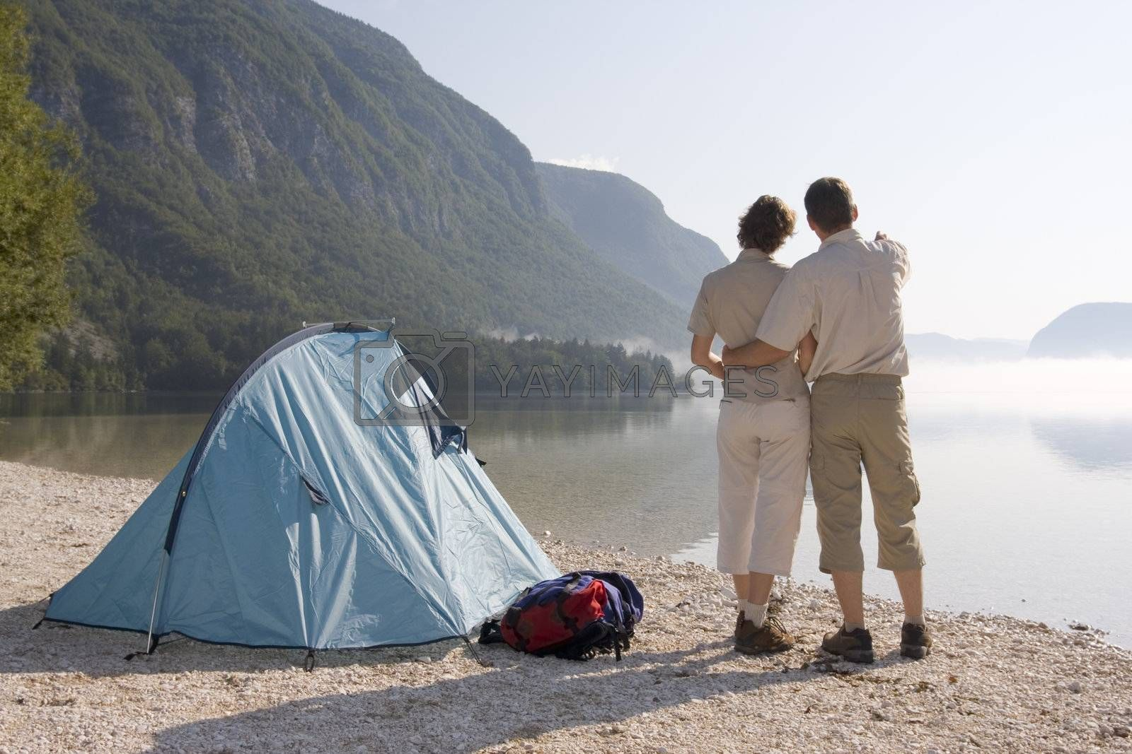 Couple standing beside a tent at a mountain lake on a misty morning