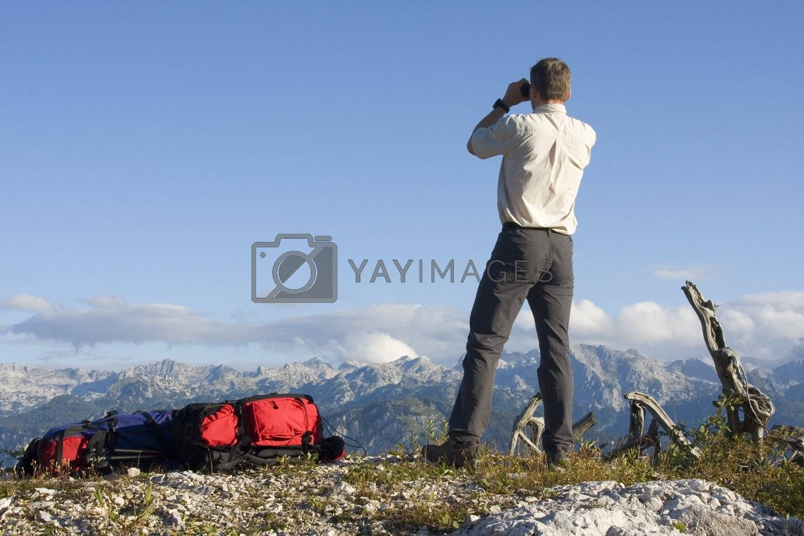 Mountaineer looking through field glasses while standing on a mountain peak