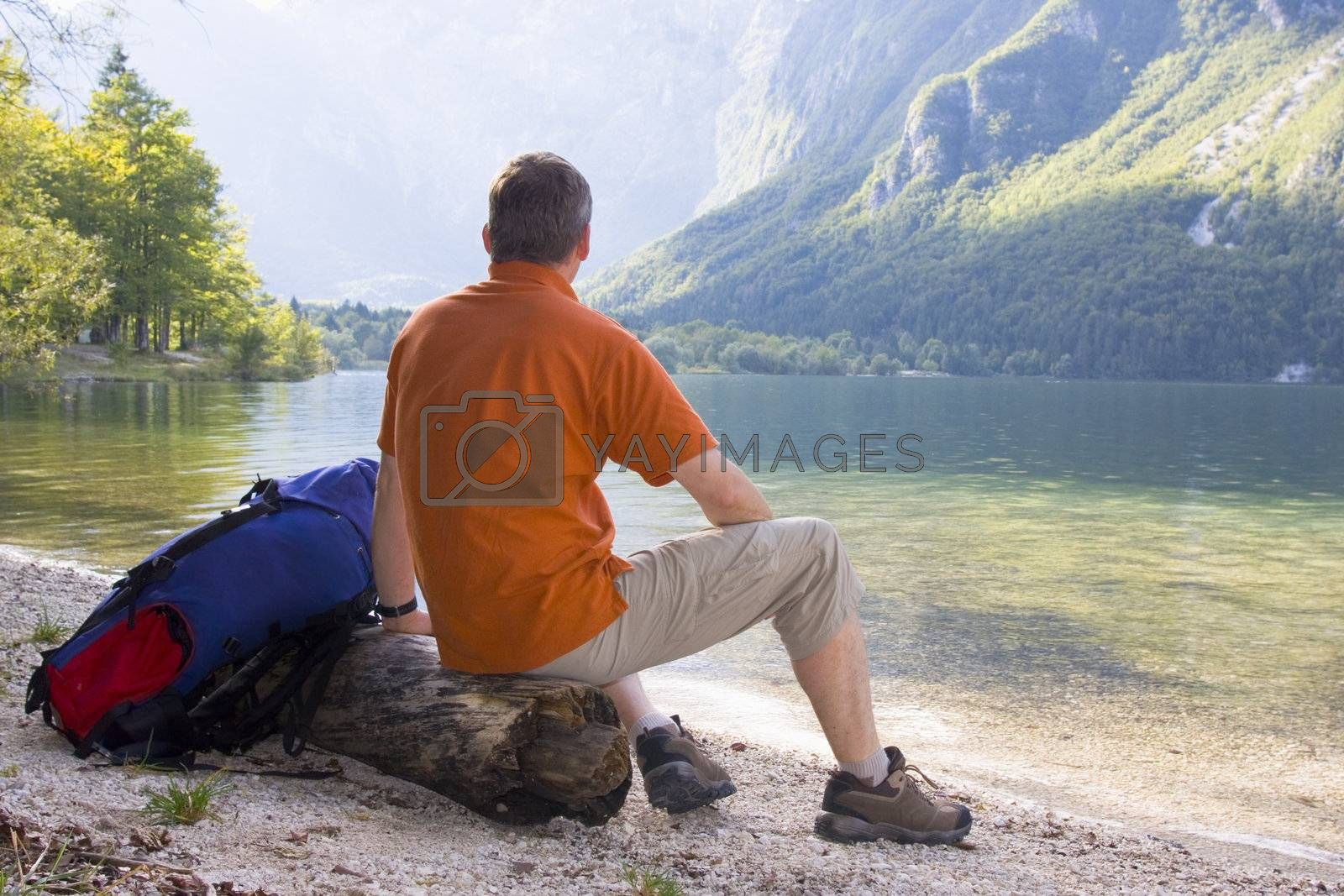 Hiker sitting on a tree trunk at a mountain lake