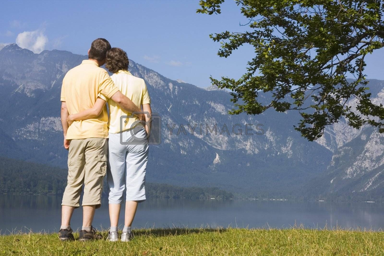 Couple contemplating a mountain lake