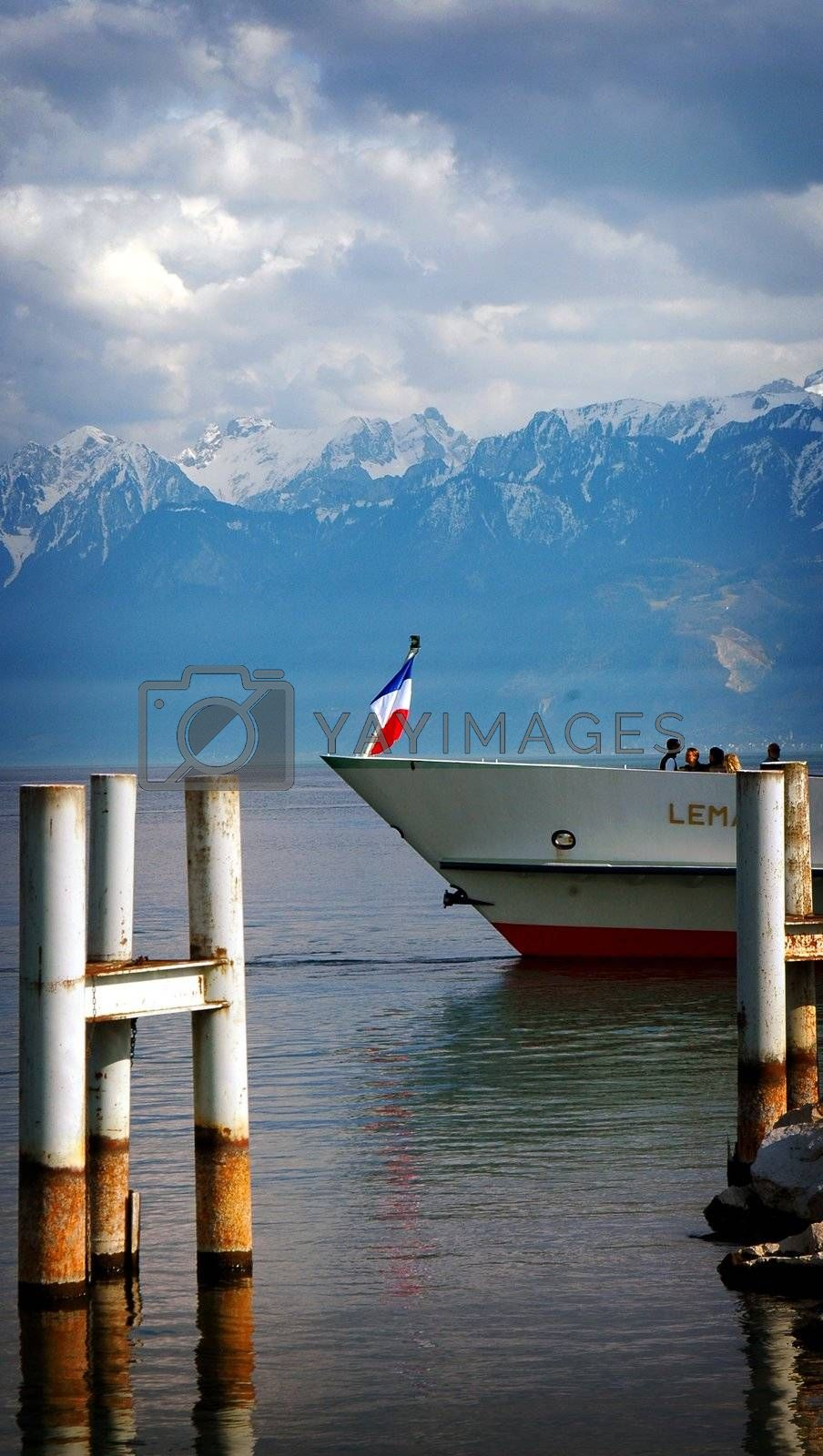 Vertical shot of front end of boat on lake Geneva, showing French Flag (France) with the French Alps in the background. Taken in March 2008 Lausanne, Switzerland.