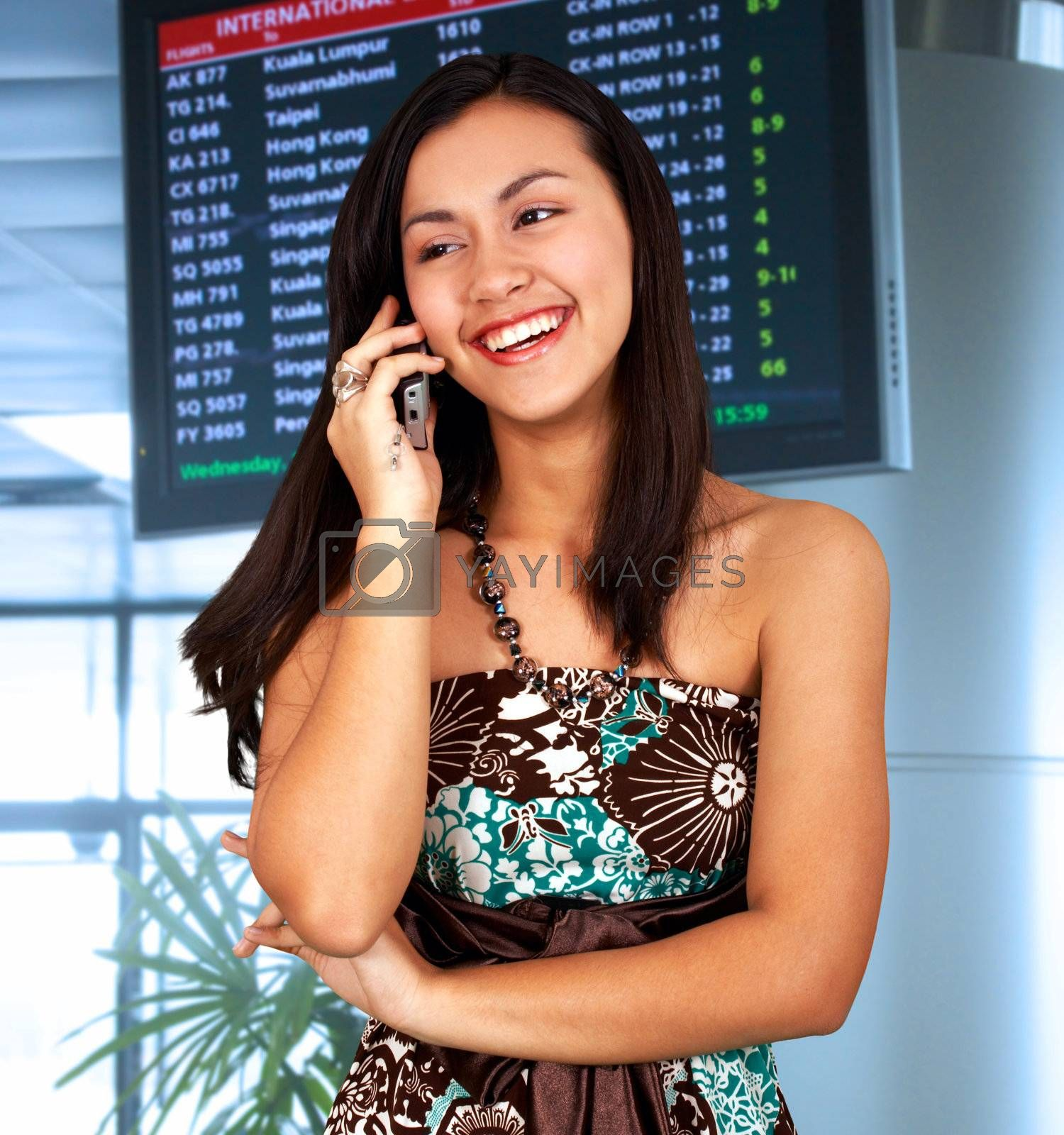 Young woman in an airport talking on the phone