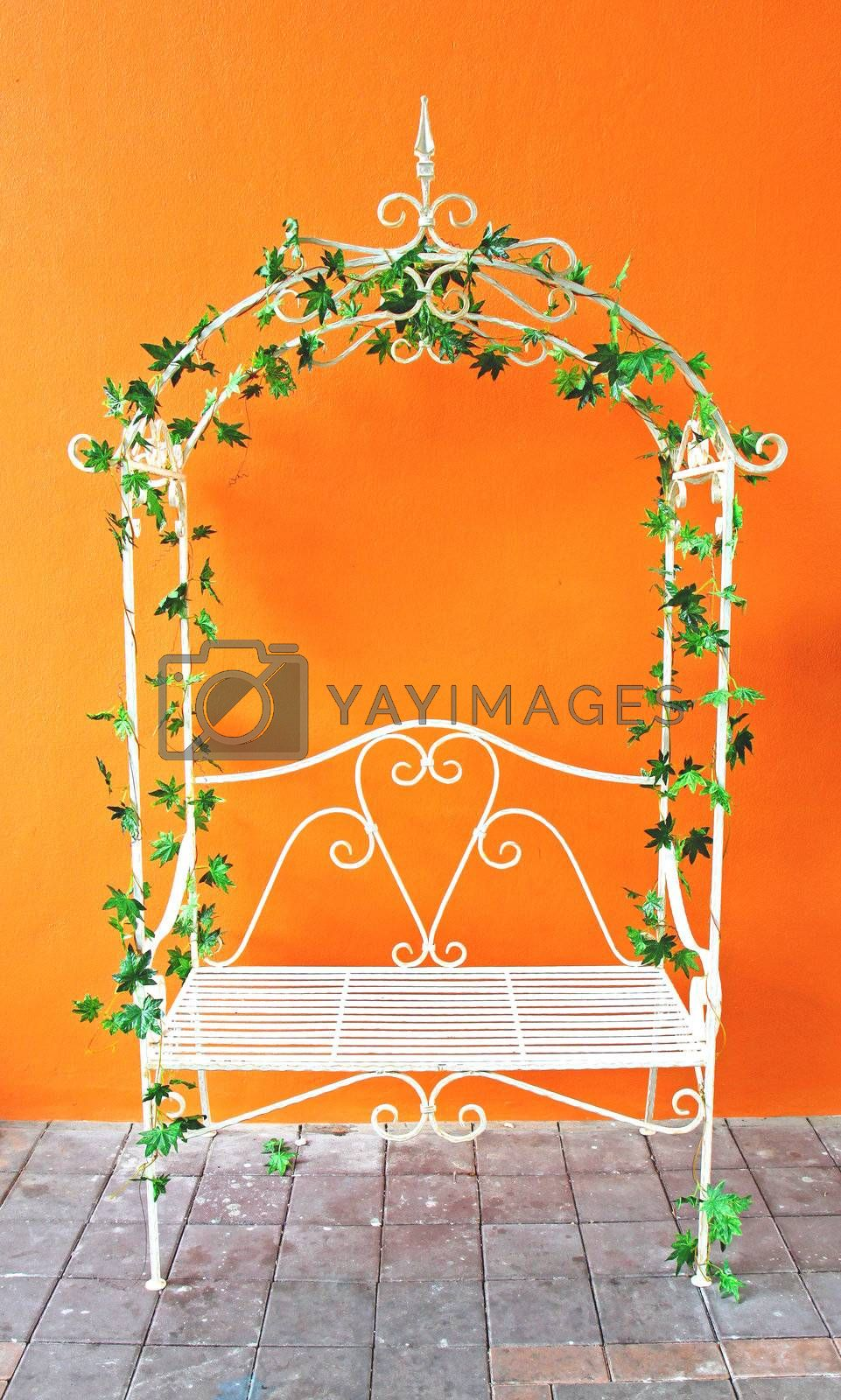 Decorated white romantic vintage chair with orange wall