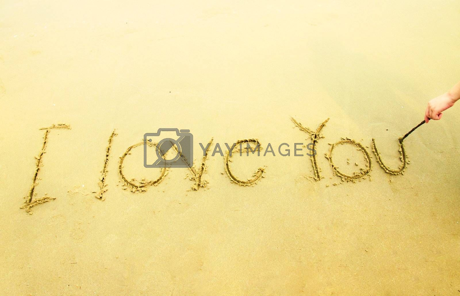 Hand writing I love you on sand at the beach