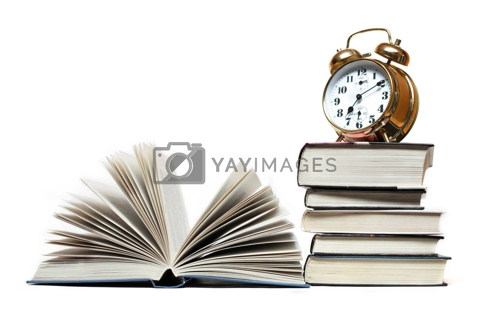 Alarm clock standing on stack of books near open book