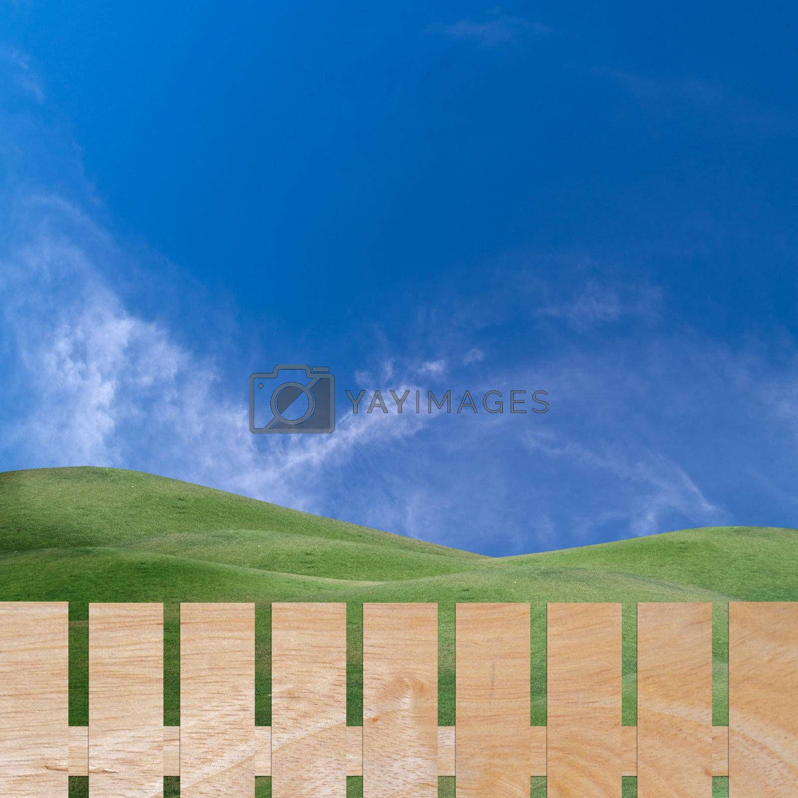 Beautiful sky over field of green hill with wooden fence