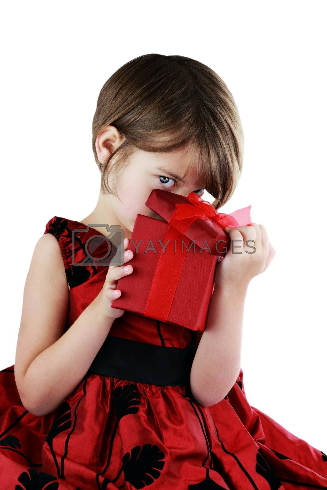 A young girl peeking into a gift she has received isolated against a white background with clipping path included.