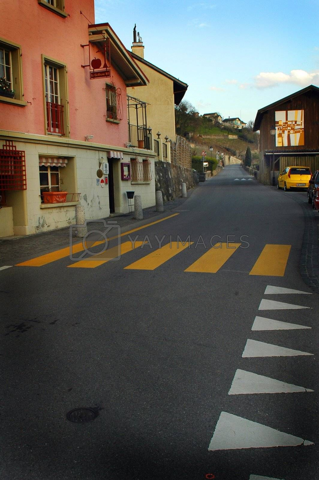 Vertical image of street crosswalks in rectangular (yellow) and triangle (white) shapes with Pink building and yellow car.