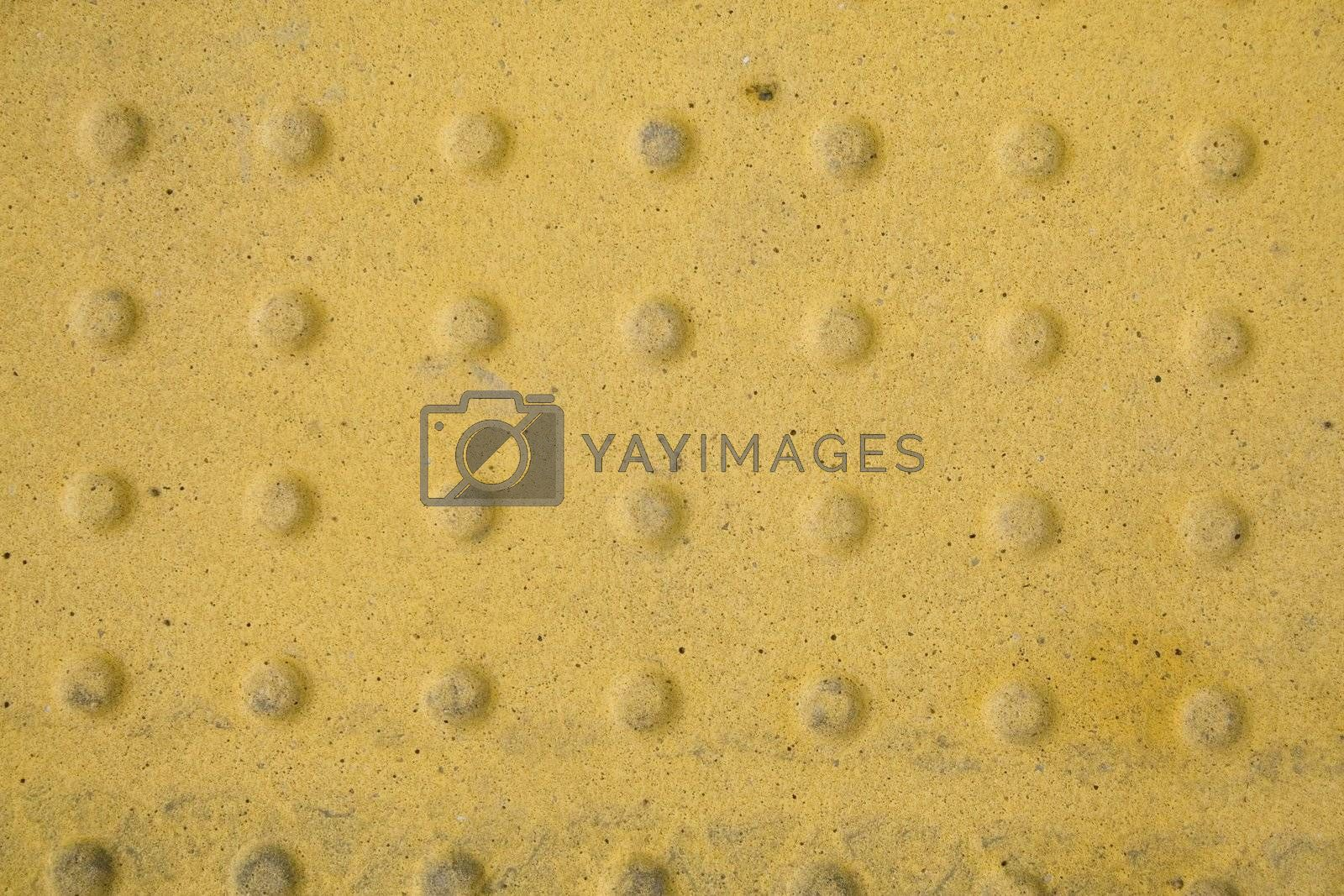 A yellow metal plate with patterned stamp.