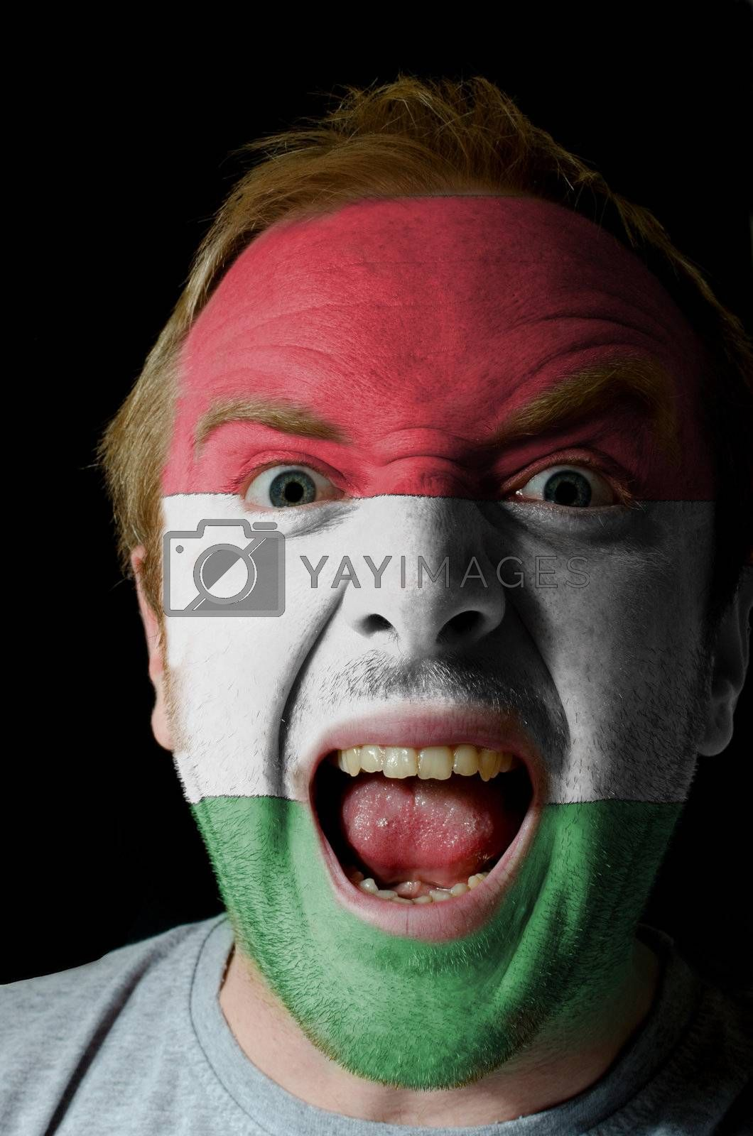 Low key portrait of an angry man whose face is painted in colors of hungary flag