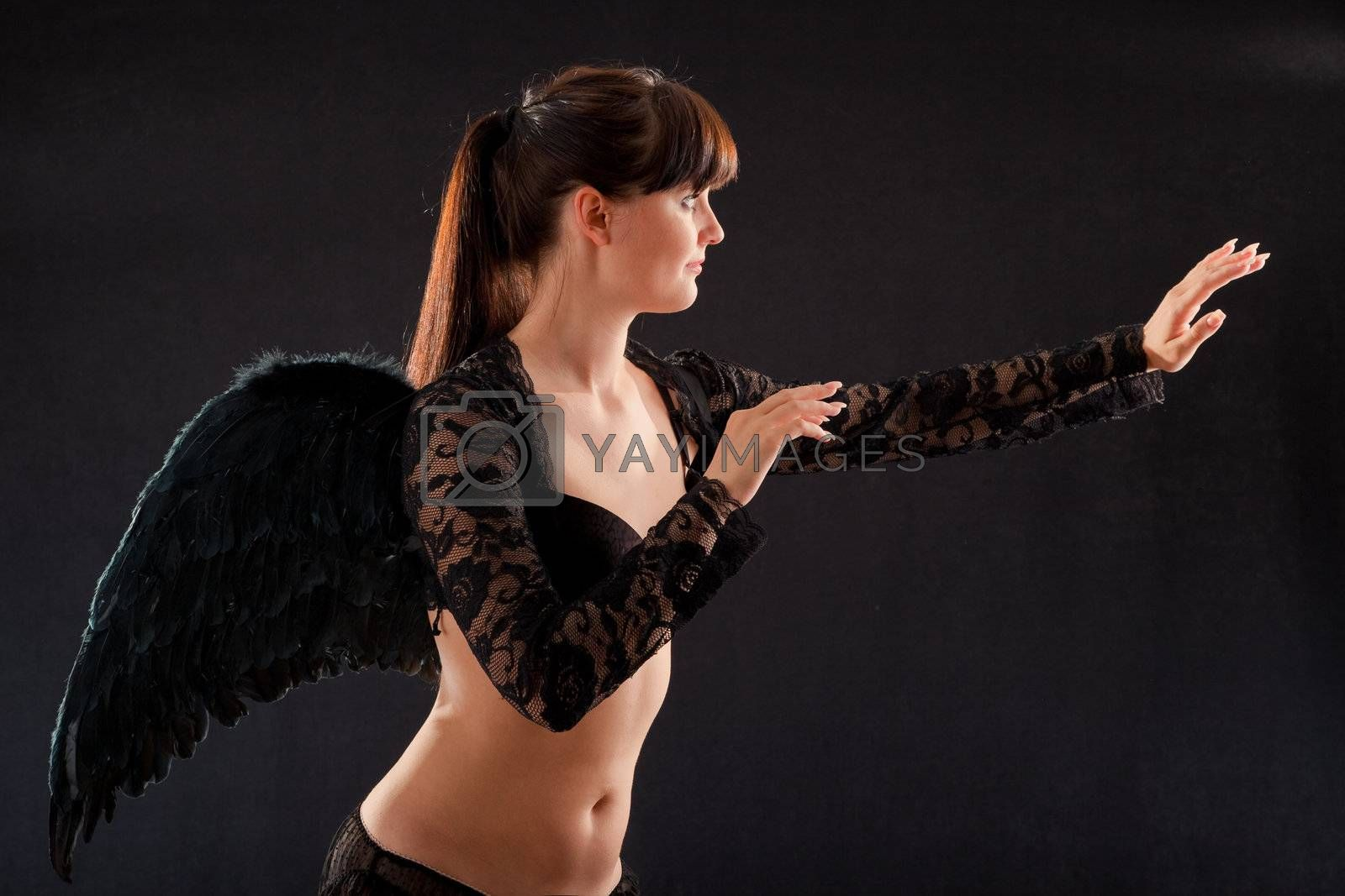 girl in black underwear and black wings on a black background