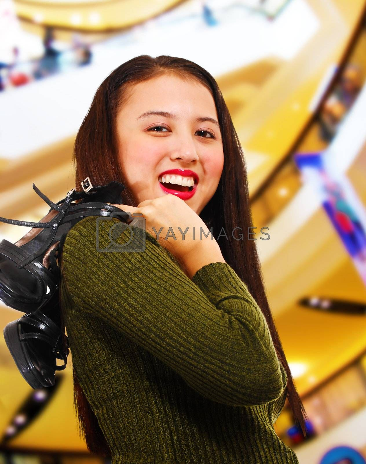 Smiling teenager in a shopping center holding her shoes over her shoulder