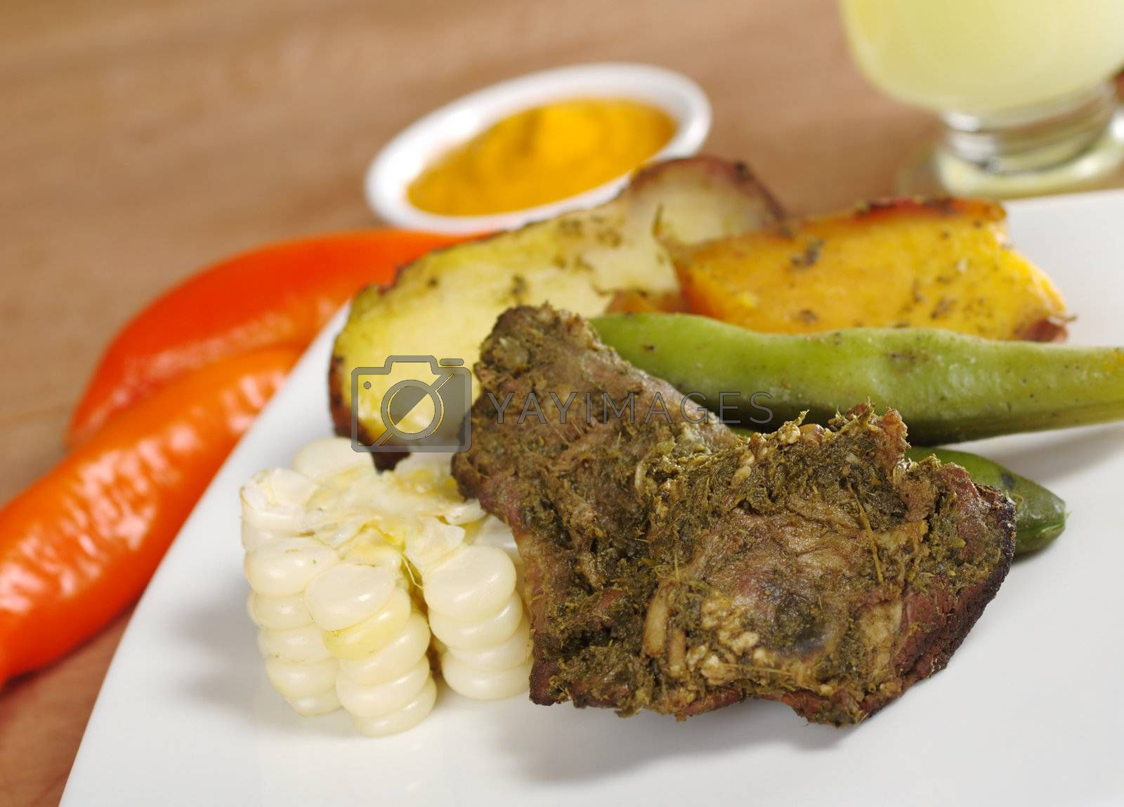 Pachamanca, which is a traditional meal from the Peruvian highlands, is made of different kinds of meat with beans and corn as well as potatoes and sweet potatoes, and is traditionally cooked in the ground (Selective Focus, Focus on the upper right part of the meat)