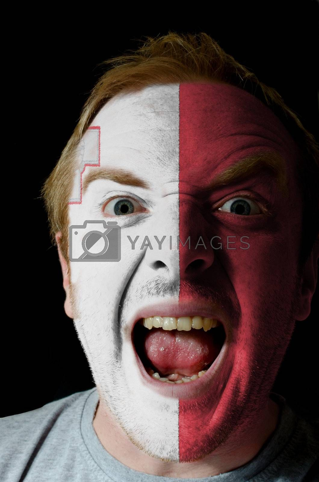 Low key portrait of an angry man whose face is painted in colors of malta flag
