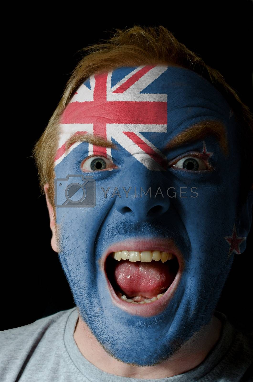Low key portrait of an angry man whose face is painted in colors of moldova flag