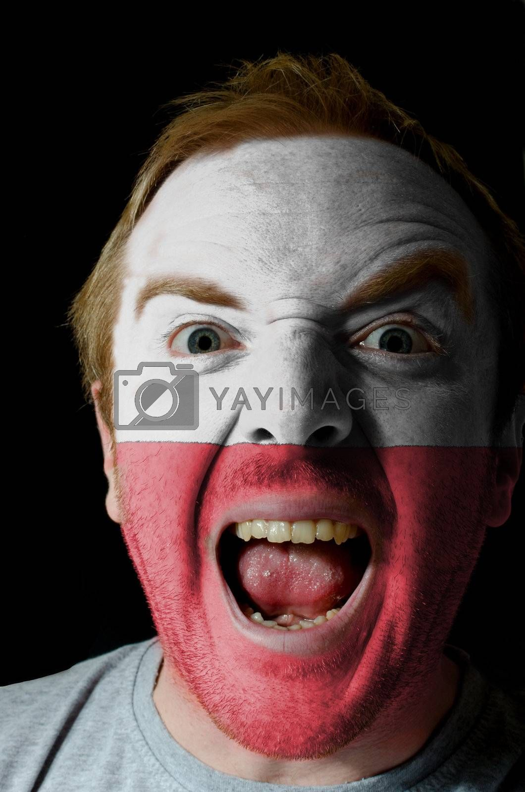 Low key portrait of an angry man whose face is painted in colors of poland flag