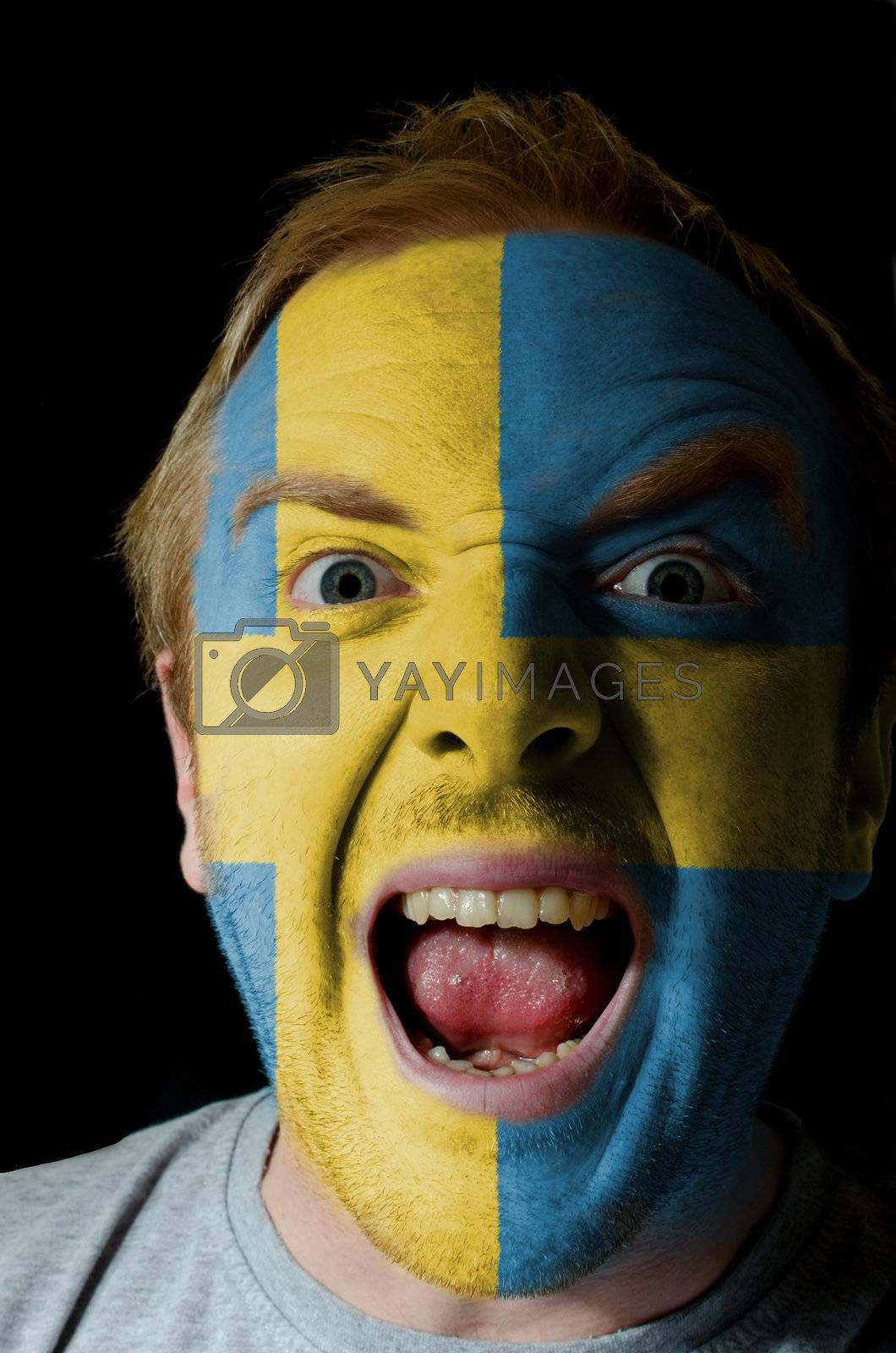 Low key portrait of an angry man whose face is painted in colors of sweden flag