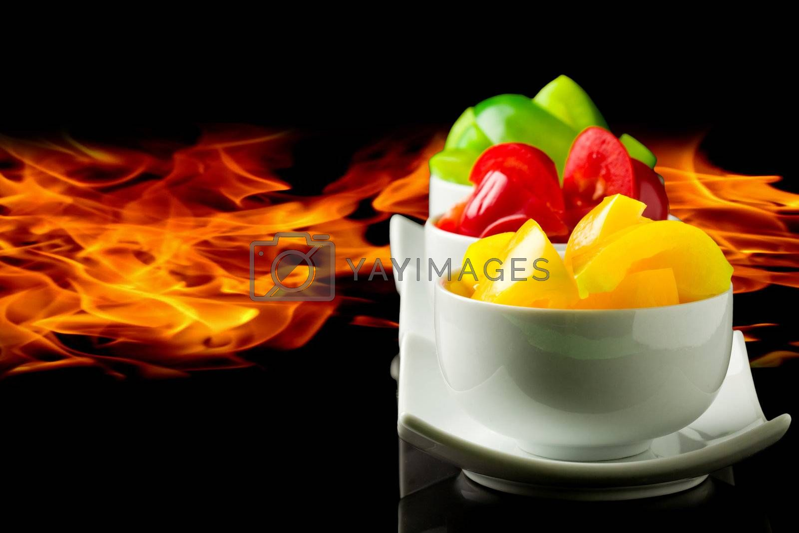 photo of colorful peppers in front of black flames background