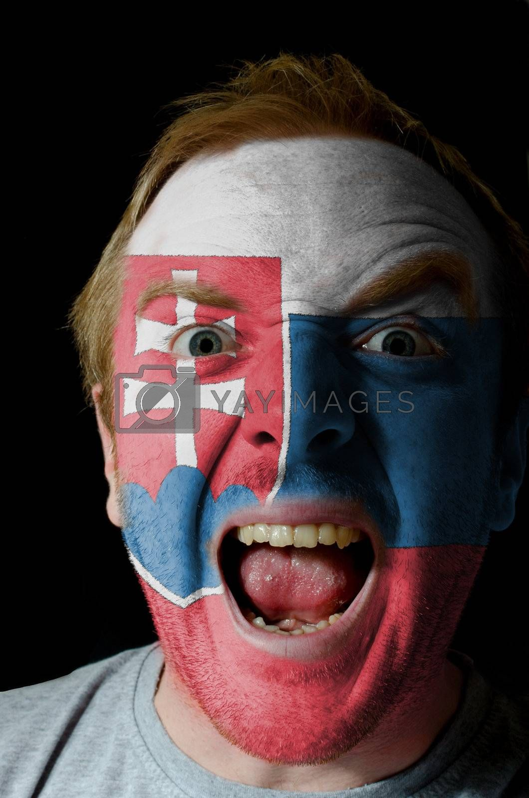 Low key portrait of an angry man whose face is painted in colors of slovakia flag