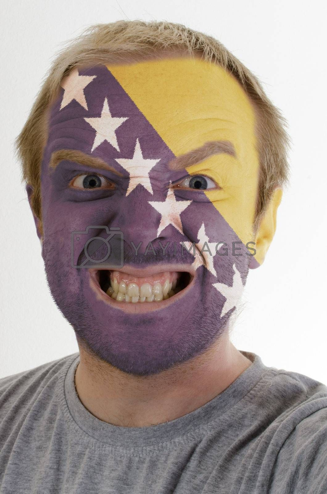 High key portrait of an angry man whose face is painted in colors of bosnia herzegovinal flag