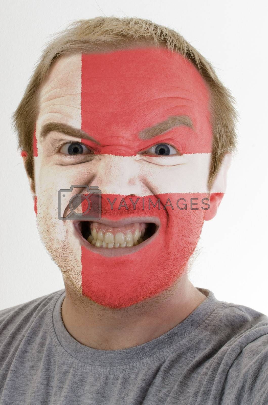 High key portrait of an angry man whose face is painted in colors of denmark flag