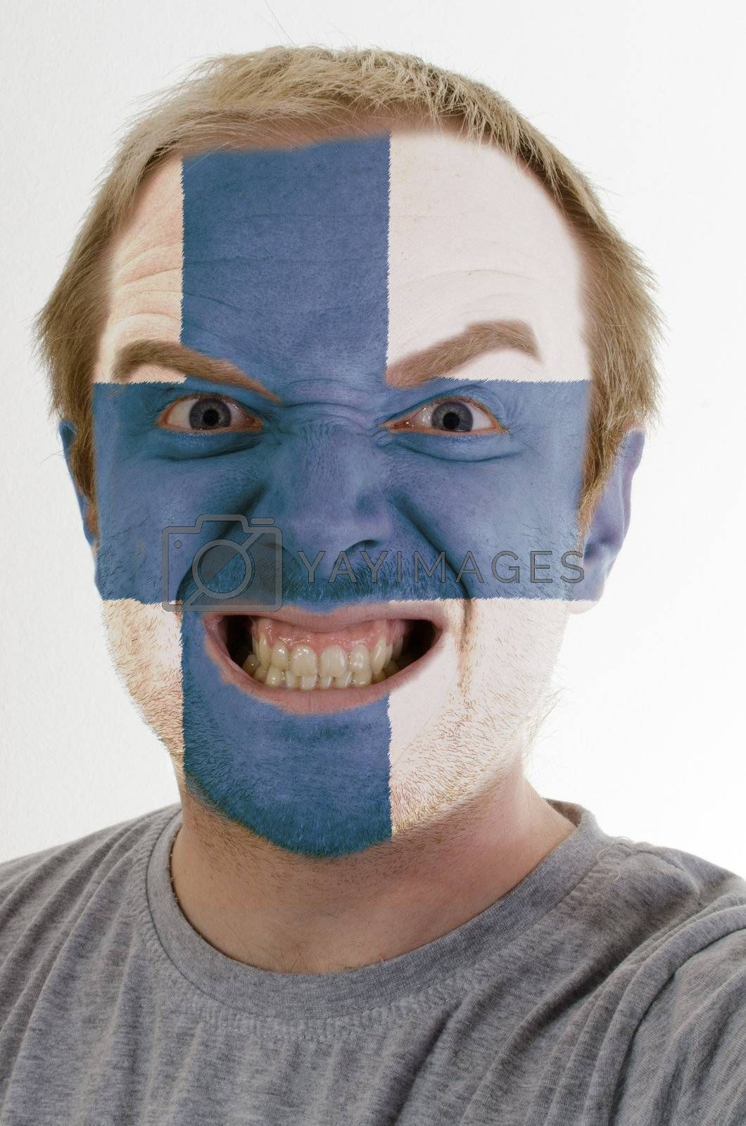High key portrait of an angry man whose face is painted in colors of finland flag