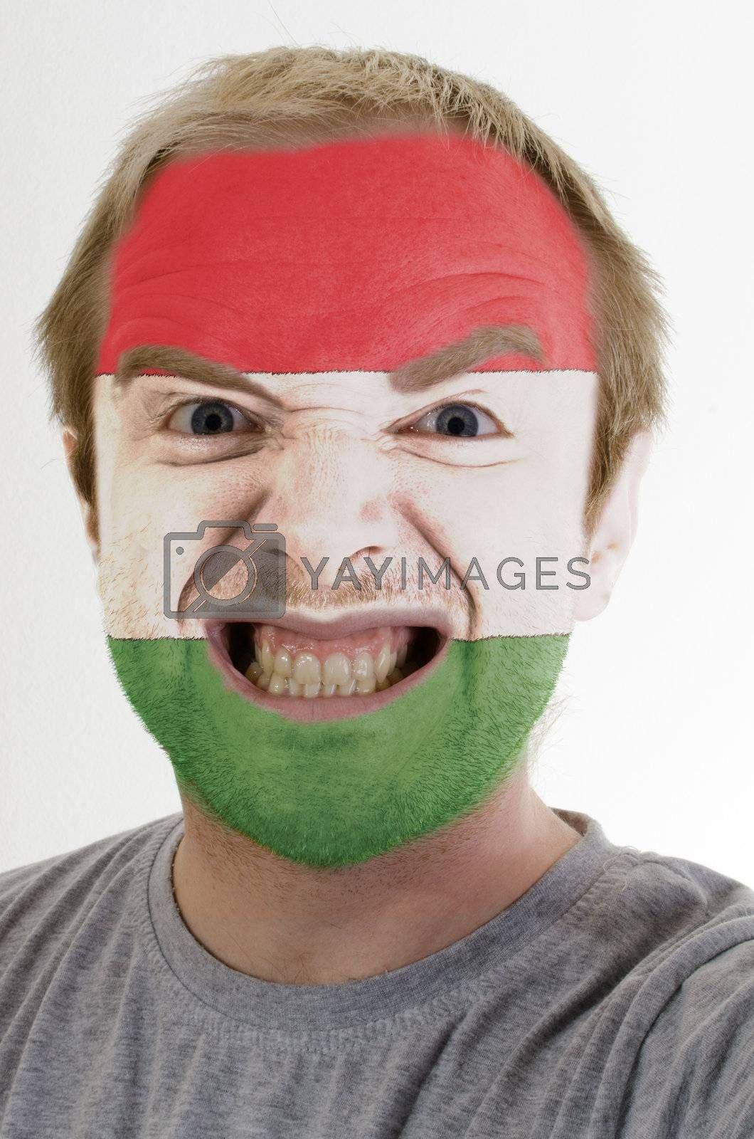 High key portrait of an angry man whose face is painted in colors of hungary flag