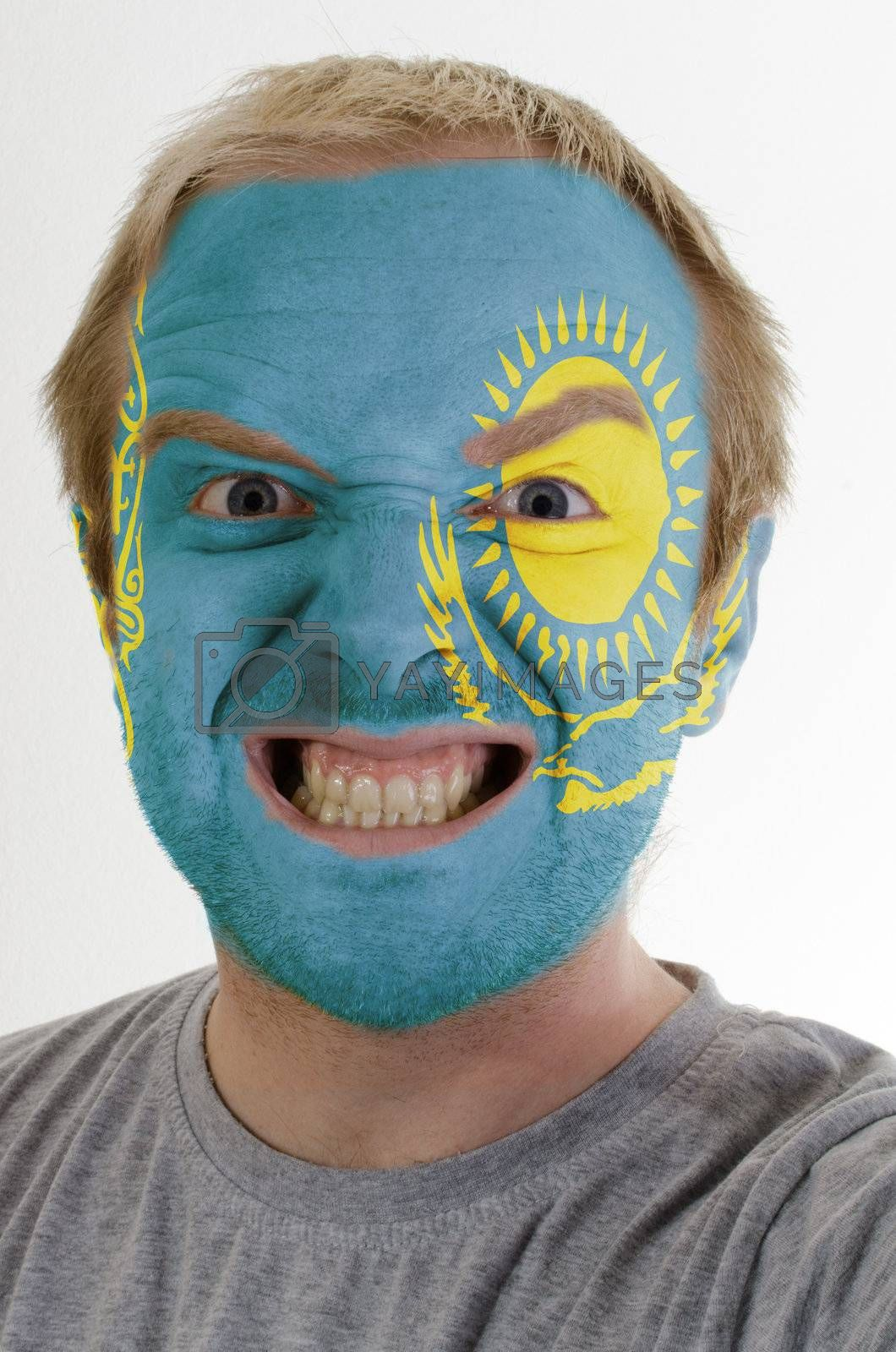 High key portrait of an angry man whose face is painted in colors of kazakstan flag