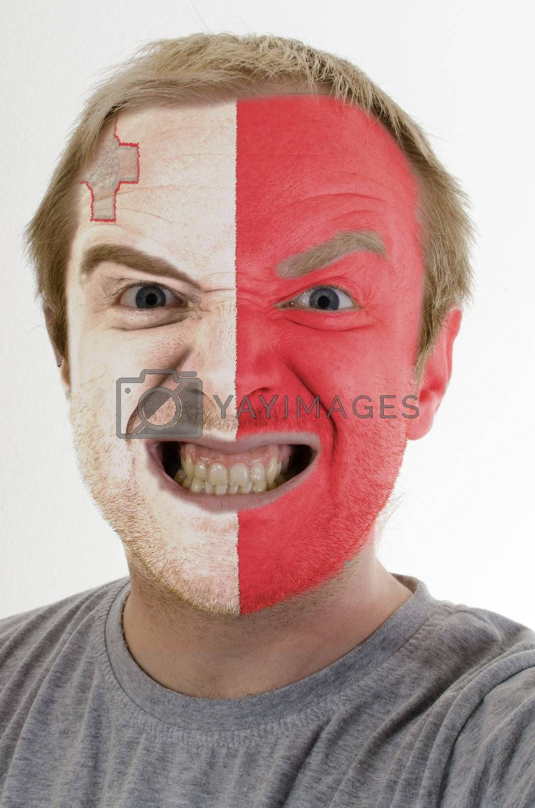 High key portrait of an angry man whose face is painted in colors of malta flag