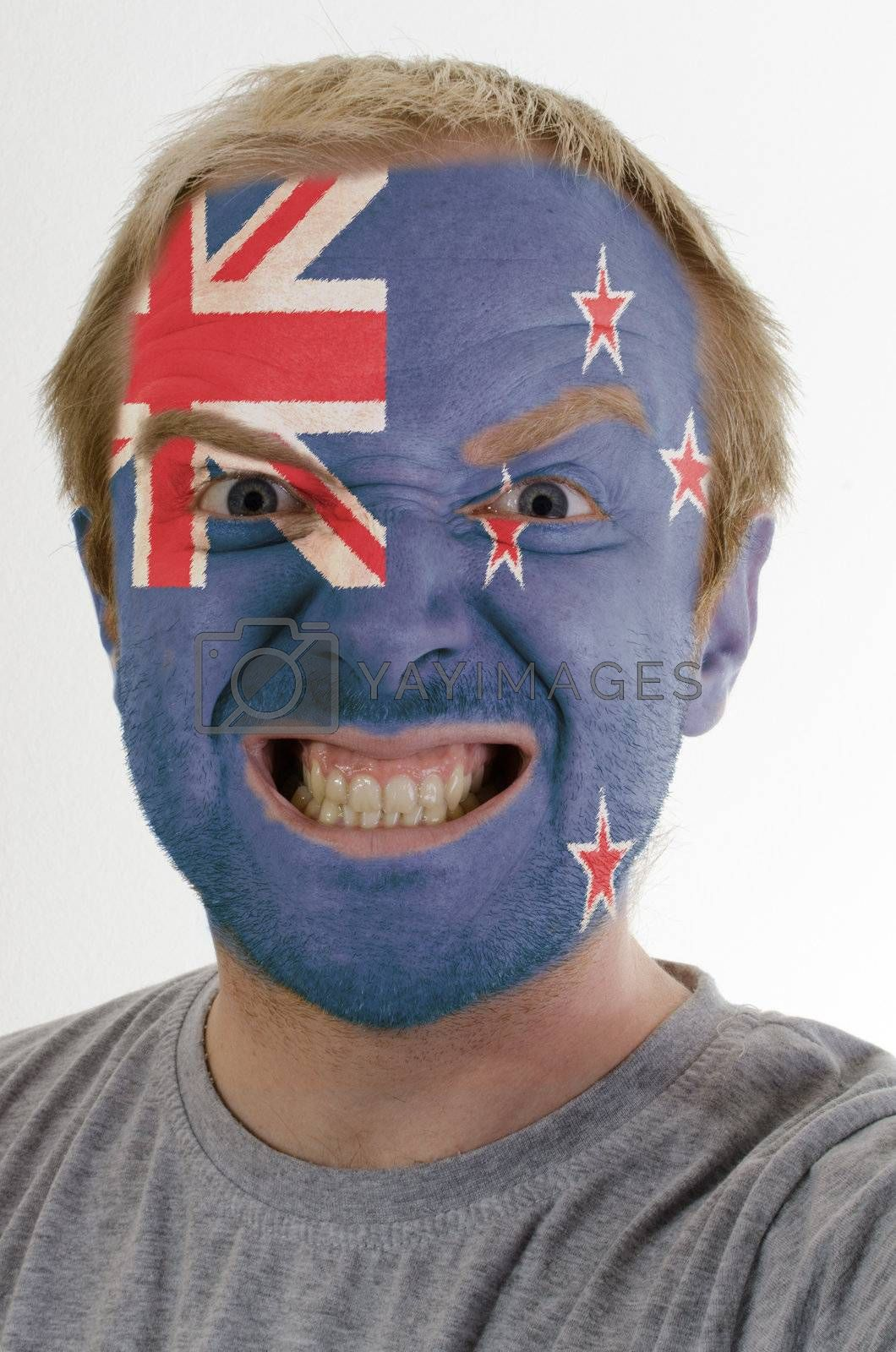 High key portrait of an angry man whose face is painted in colors of new zealand flag