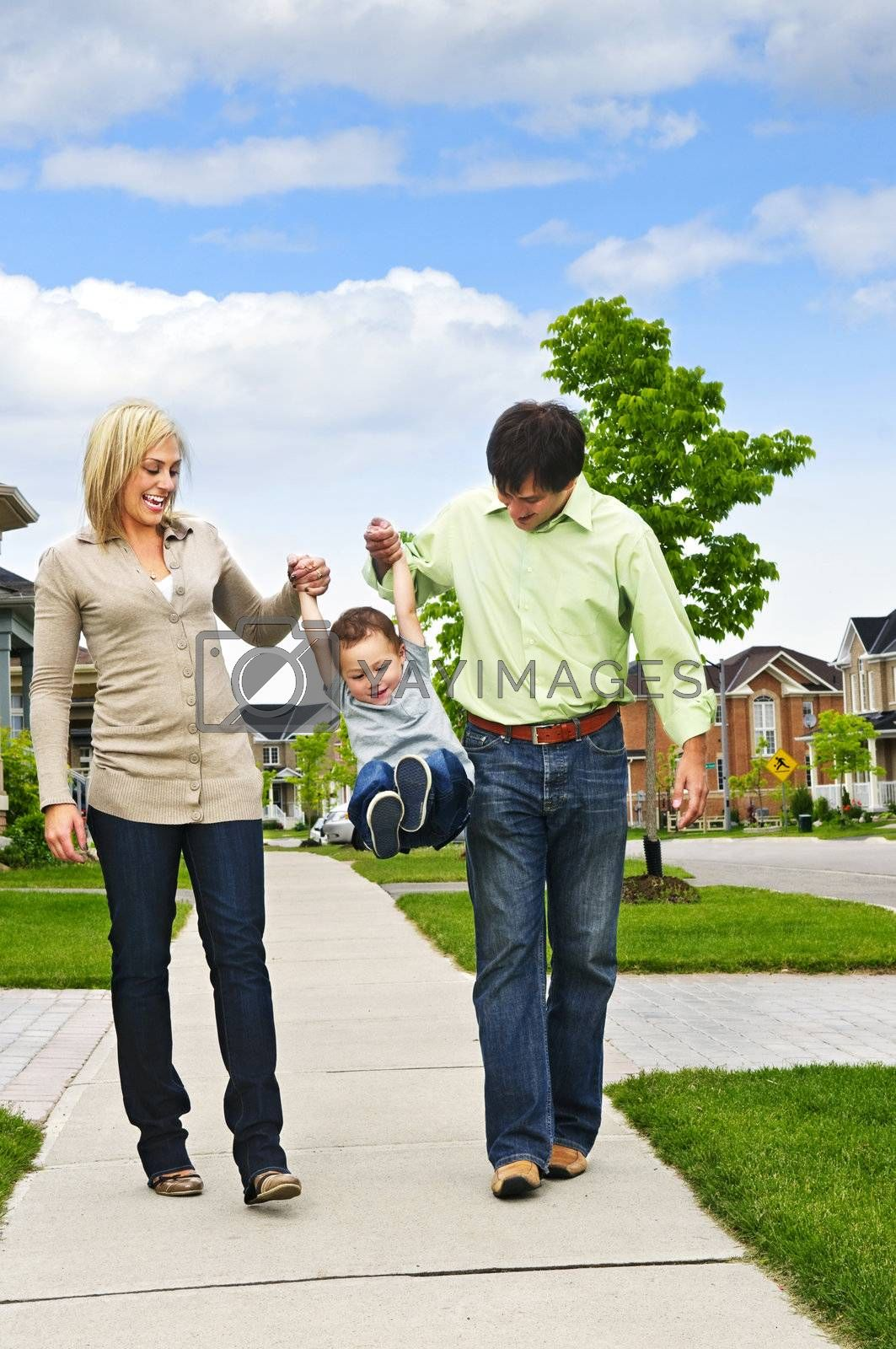 Young happy family playing with son on sidewalk