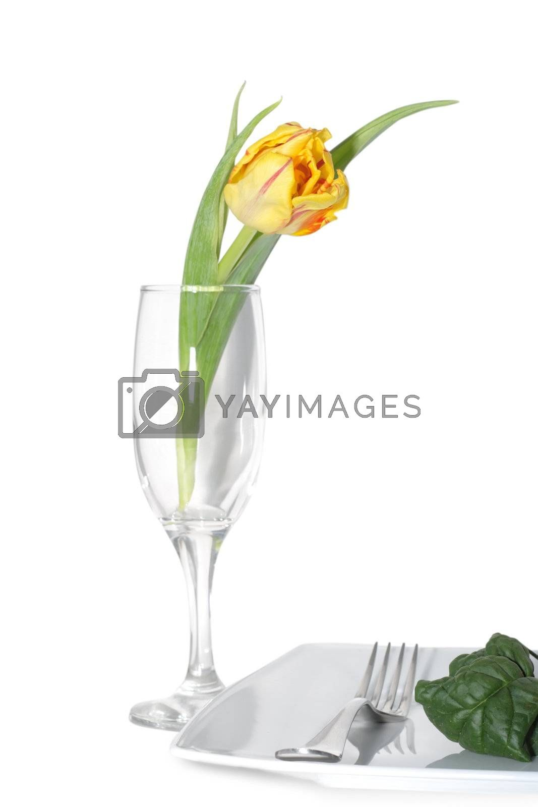 Still life of vegetables on a plete and flower in a glass.