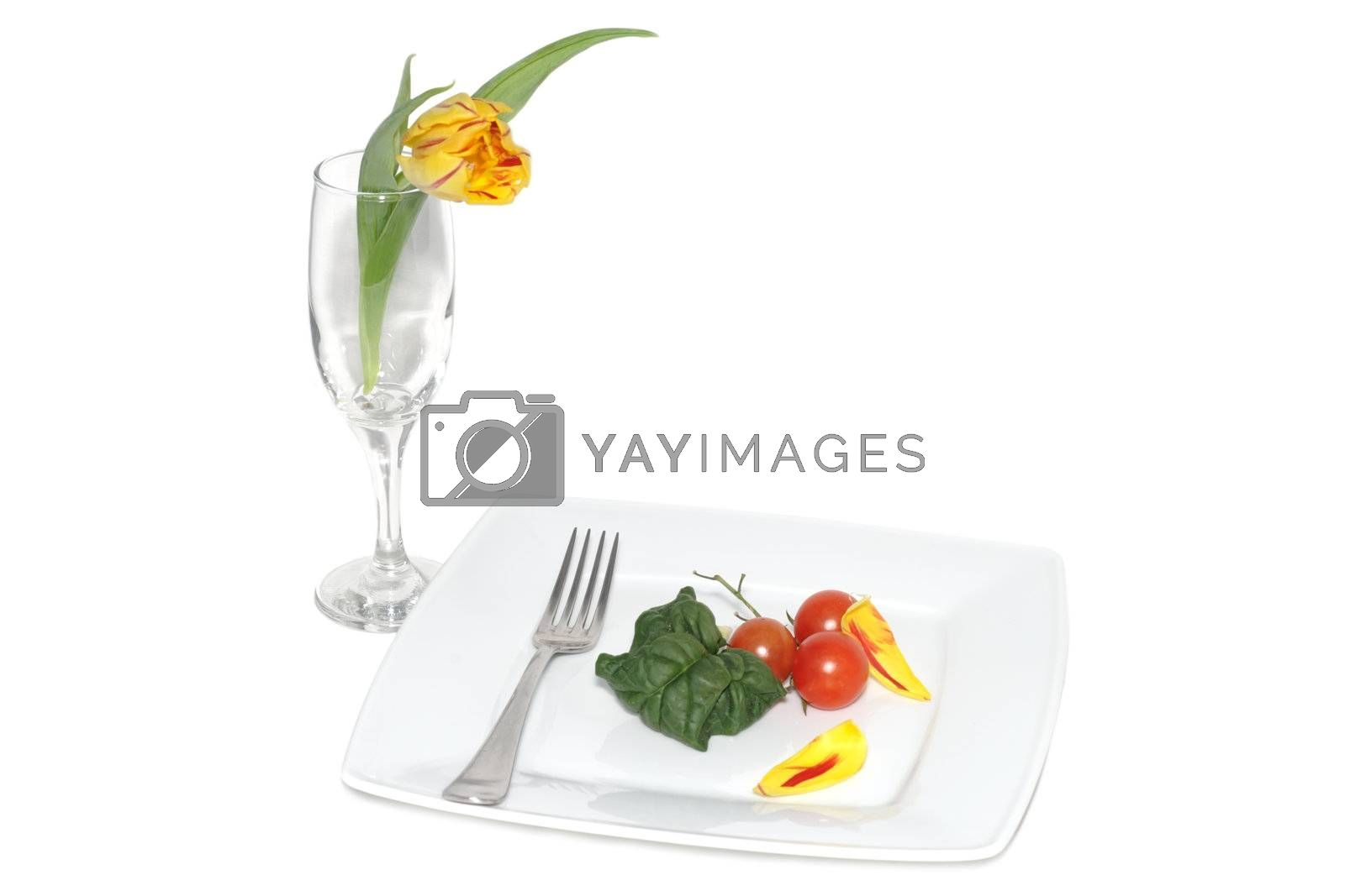 Still life of vegetables on a plete and flower in a glass